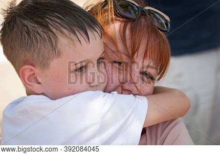 Cute Blonde Caucasian Boy With Blue Eyes Embracing His Beloved Mother. Woman With Red Hair Smiles At