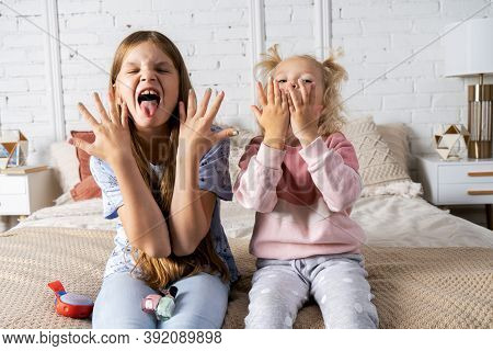 Two Girls Are Sitting On The Bed In The Bedroom And Showing Off Their New Manicure.