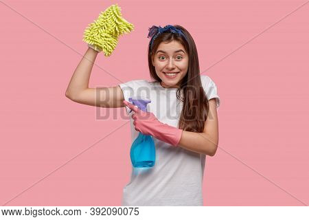 Positive Young Woman Shows Muscles After Tired Work About House, Dressed In White Casual T Shirt, Ho