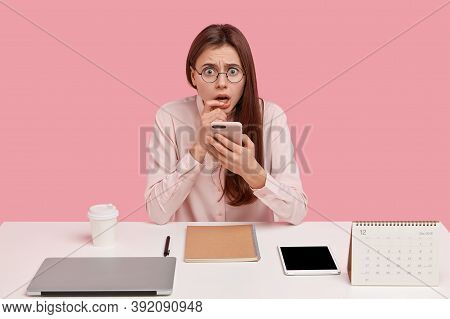 Indoor Shot Of Frightened Displeased Woman Holds Mobile Phone, Has Everything Neatly Arranged On Tab