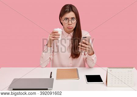 Upset Brunette Female Office Perfectionist Has Unhappy Expression, Drinks Takeaway Coffee, Holds Mob