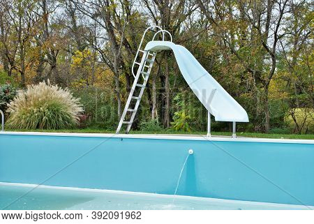 Backyard Swimming Pool With Pool Slide Emptied Out Shutting Down For Winter