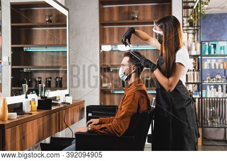 Side View Of Hairstylist In Face Shield And Latex Gloves Cutting Hair Of Client In Medical Mask, Sto