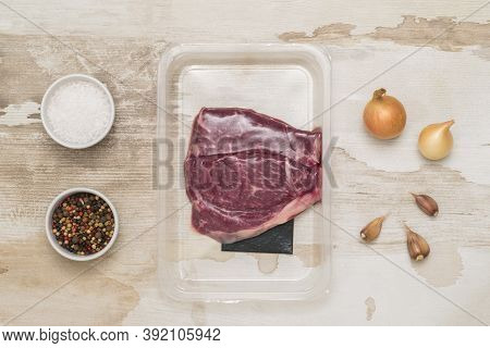 Salt, Pepper And Beef Steaks In Vacuum Packaging On A Wooden Table. Sealed Packaging For Meat.