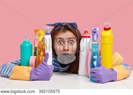 Horrified Young Female Has Eyes Popped Out, Keeps Sponge In Mouth, Embraces Cleaning Supplies, Stupe