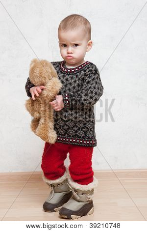 Baby in winter clothes with toy