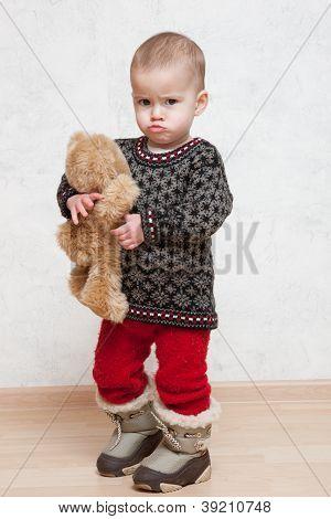 Baby auf Winterkleidung mit Spielzeug