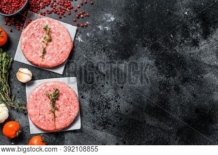 Burger Patties, Raw Fresh Ground, Mince Meat. Black Background. Top View. Copy Space