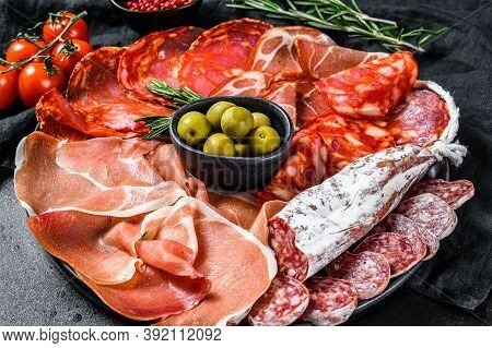Cured Meat Platter Of Traditional Spanish Tapas. Chorizo, Jamon Serrano, Lomo And Fuet. Black Backgr