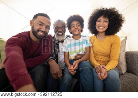 Portrait of multi generation African American family at home sitting on sofa in living room, smiling to camera. Family spending quality time at home together in slow motion.