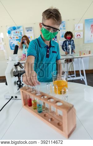 Portrait of a schoolboy wearing a face mask and looking at multiple probes. Education back to school health safety during Covid19 Coronavirus pandemic.