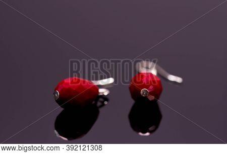 Pair Of Red Bijou Earring Close Up Macro Shot On Reflecting Magenta Background.