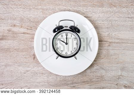 Top View Alarm Clock On White Plate On Wooden Table Background. Intermittent Fasting, Ketogenic Diet