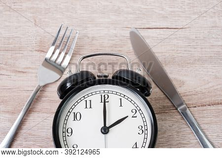 Top View Alarm Clock With Knife And Fork On Wooden Table Background. Intermittent Fasting, Ketogenic
