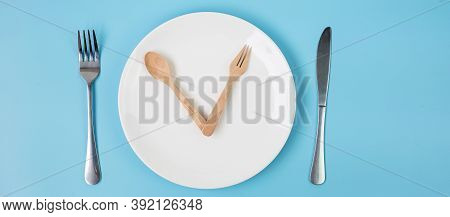 Top View White Ceramic Plate With Knife, Spoon And Fork On Blue Background. Intermittent Fasting, Ke