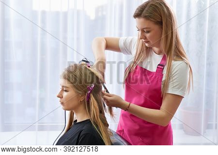 Hairdresser Makes Hairstyle Girl With Long Hair In A Beauty Salon. Create Curls With Curling Irons