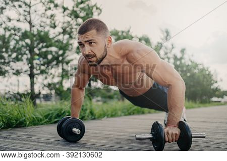 Muscular Male Bodybuilder Does Push Up With Barbells Stands In Palnk Pose With Naked Body, Trains De