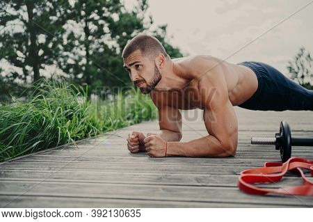 Muscular Bodybuilder Stands In Plank Pose Demonstrates Endurance Has Strong Biceps Poses Outdoor Has