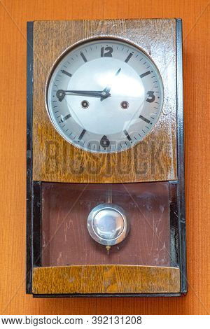 Retro Wooden Clock With Pendulum At Wall