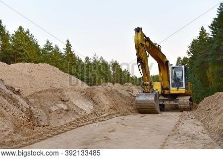 Excavator During Construction New Road In Forest Area. Backhoe At Groundwork. Earth-moving Equipment