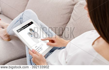 Lady Shopping Online Using Digital Tablet Buying Sneakers In Internet Shop Sitting On Sofa At Home.