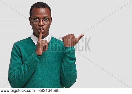 Horizontal Shot Of Dark Skinned Secret Man Makes Silence Gesture, Points Aside, Demonstrates Shush S