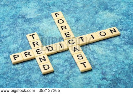 prediction, forecast and trend crossword in ivory letter tiles against textured handmade paper, science, business and analytics concept