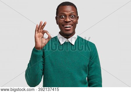 Horizontal View Of Attractive Young Black Man With Toothy Smile, Shows Okay Gesture, Says Alright, L