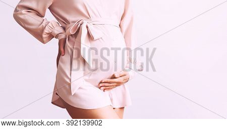 Beautiful Pregnant Woman Holds Hands On Belly On White Background. Loving Mother Waiting For Baby Bi