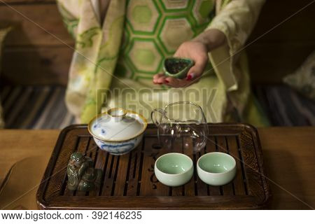 A Girl In A Japanese Kimono Is Holding A Bowl With Chinese Lujing Tea. Table With Bowls, A Wooden Tr