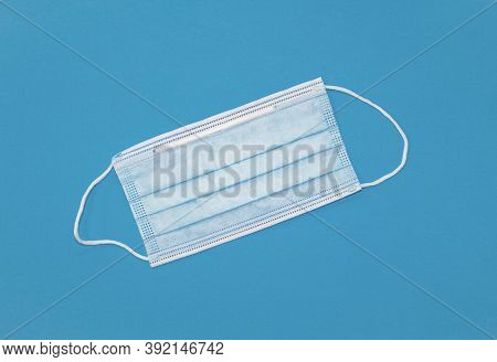 Disposable Face Mask Lying On A Blue Background. View From Above.