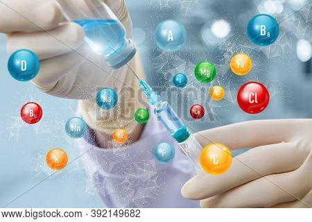 Vitamin Complex Injection Concepts. Syringe In Hand Against The Background Of Vitamins.