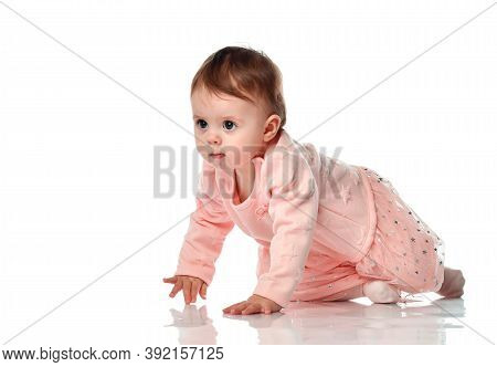 Serious Cute Little Baby Girl Creeping Forward Looking Ahead. Adorable Little Caucasian Child Moving