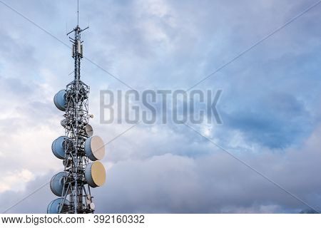 Telecommunication, Television And Radio Antennas Isolated Over Dramatic Sky With Clouds. Industry An