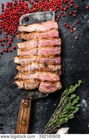 Sliced Marble Pork Cutlet Steak With And Herbs. Black Background. Top View.
