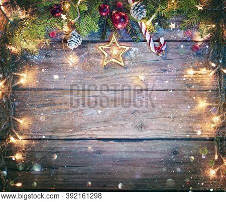 Rustic Christmas Board - Fir Branches And String Light On Wooden Plank With Defocused Abstract Snowf