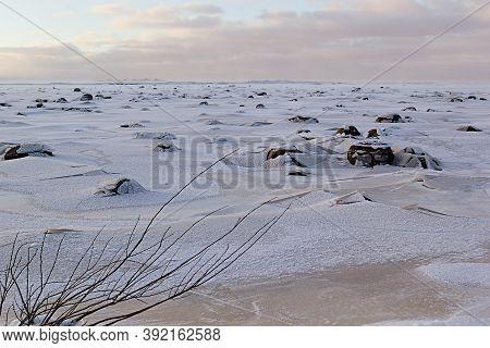 Minimalist North Cold Landscape In Winter With Frozen Shore, Crack Broken Ice, Black Stones, Horizon