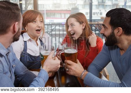 Group Of Friends Talking While Having Beer Together At Local Pub