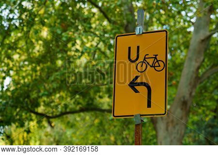 Yellow Rectangular Sign Of The Bike Bypass Road Against The Background Of Foliage Trees. Close-up.