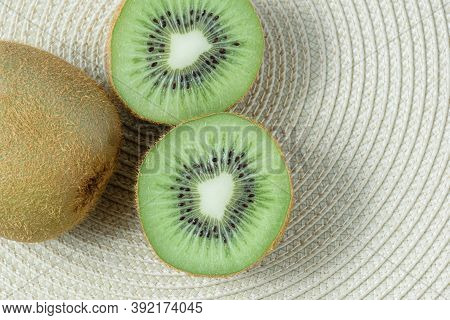 Two Kiwis On A Straw Placemat In A Circular Shape_top View.