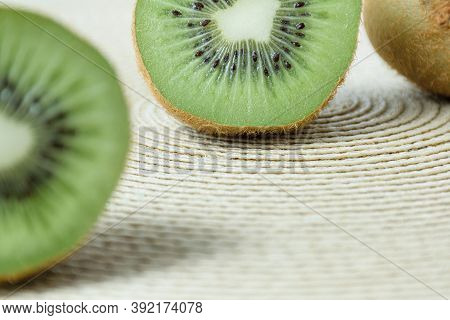 Half A Kiwi Defocused In The Foreground, In The Background The Other Half Of The Fruit On A Straw Pl