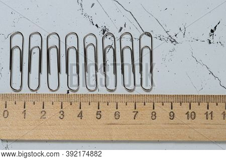 Office Supplies, Nickel-plated Paper Clips On The Textured Surface Of The Table. Selective Focus.