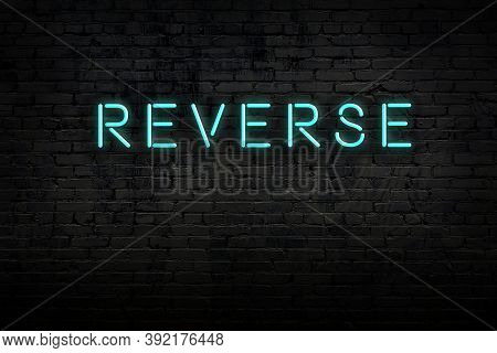 Neon Sign With Inscription Reverse Against Brick Wall. Night View