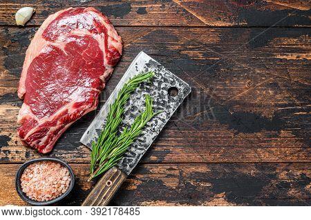Raw Cowboy Or Rib Eye Steak On The Bone On A Meat Cleaver. Marble Beef Meat Ribeye. Dark Wooden Back