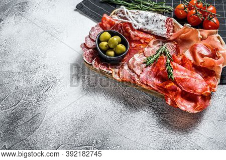 Spanish Cold Meat Assortment. Chorizo, Fuet, Lomo, Jamon Iberico, Olives. Gray Background. Top View.