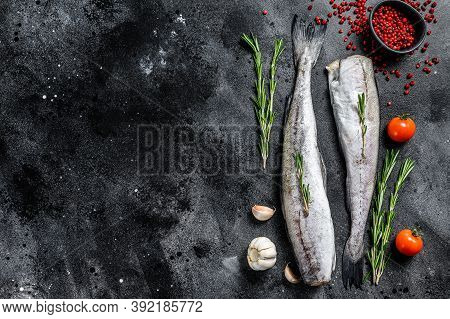 Raw Pollock Fish With Rosemary And Pink Pepper. Organic Seafood. Black Background. Top View. Copy Sp