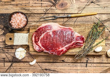 Rib Eye Or Cowboy Steak. Raw Marble Beef Black Angus, Ribeye. Wooden Background. Top View