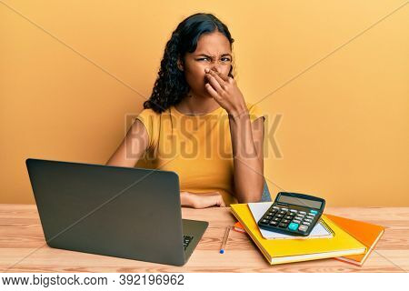 Young african american girl working at the office with laptop and calculator smelling something stinky and disgusting, intolerable smell, holding breath with fingers on nose. bad smell