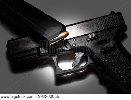A Semi Automatic Black 9mm Pistol With A Loaded Pistol Magazine Laying On Top Of It On A Gray Backgr