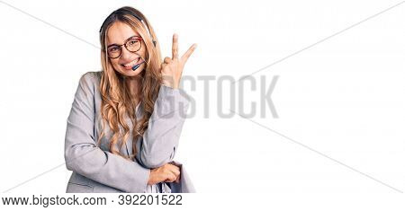 Young beautiful blonde woman wearing call center agent headset smiling with happy face winking at the camera doing victory sign. number two.